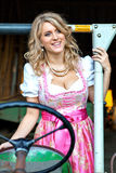 Pretty young Bavarian woman with Dirndl dress on a tractor Royalty Free Stock Photography