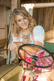 Pretty young Bavarian woman with Dirndl dress on a tractor Stock Photography