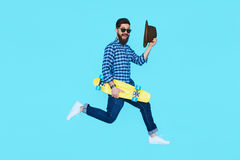 Pretty young bearded man jumping with yellow skateboard. Against the colorful wall. Hipster in motion on blue background Stock Image