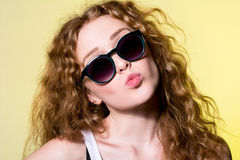 Pretty young beautiful girl in sunglasses makes lips kiss Royalty Free Stock Image
