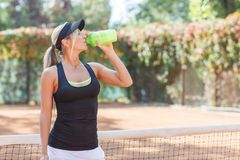 Pretty young female tennis player drinking water eyes closed. Royalty Free Stock Photo