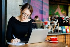 Pretty young beautiful woman in glasses using laptop in cafe, close up portrait of business woman, a computer, financial analyst,. A sales manager, prepares a royalty free stock photography