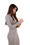 Pretty young beautiful woman writing, holding notebook organizer Stock Photography