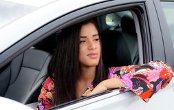 Pretty Young Black Woman in Car. A portrait of a young woman in a 1960s inspired dress, looking out a car window Royalty Free Stock Photo