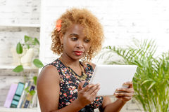 A pretty young black woman  looking a digital table Stock Photo