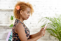 A pretty young black woman  looking a digital table Stock Image
