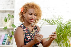 A pretty young black womanlooking a digital table Royalty Free Stock Image