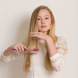Pretty Young Blond Girl Brushing Her Hair Royalty Free Stock Images