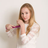 Pretty Young Blond Girl Brushing Her Hair Royalty Free Stock Photo