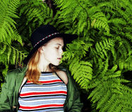 Pretty young blond girl hipster in hat among fern, vacation in g. Reen forest close up Royalty Free Stock Image
