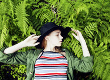 Pretty young blond girl hipster in hat among fern, vacation in green forest Royalty Free Stock Images