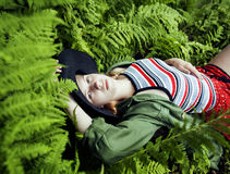 Pretty young blond girl hipster in hat among fern, vacation in green forest Royalty Free Stock Image