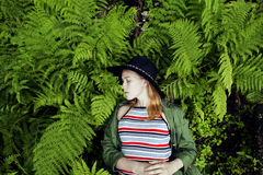 Pretty young blond girl hipster in hat among fern, vacation in green forest Royalty Free Stock Photos