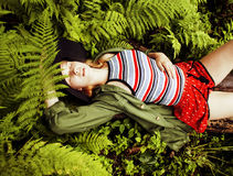Pretty young blond girl hipster in hat among fern, vacation in green forest, lifestyle fashion people concept Royalty Free Stock Images