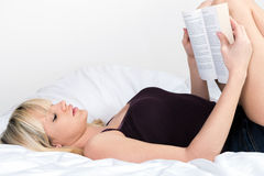 Pretty young blond girl reading book lying in her bed Stock Images