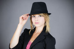 Pretty young blond with hat. Cute young blond teenager girl model wearing a black felt hat and coat, studio shot over grey background Stock Photos