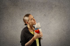 Pretty young blond woman in casual cloths holds in arms plush cat toy with heart, dreaming, looking up, missing somebody Royalty Free Stock Images