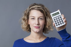 Pretty young blond woman holding calculator Stock Photos