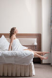 Pretty young blond woman stand from bed Stock Photos