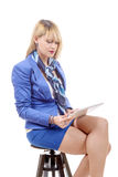 Pretty young blond woman with tablet, sitting on a stool Stock Photos