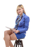 Pretty young blond woman with a tablet, sitting on a stool Stock Photos