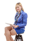 Pretty young blond woman with a tablet, sitting on a stool Stock Photography
