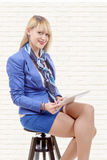 Pretty young blond woman with tablet, sitting on a stool Stock Photo
