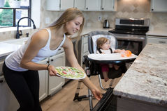 Pretty young blond woman taking delicious pizza out of oven. Royalty Free Stock Images
