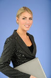 Pretty Young Blonde Business woman. Beautiful young blonde business woman in grey suit holding laptop computer and smiling blue background stock photography