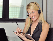 Pretty young blonde business woman. Beautiful young blonde woman sitting in office with headphones - smiling - wearing a vest and taking notes on a clipboard Stock Photography