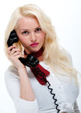 Pretty young blonde female on old phone Stock Images