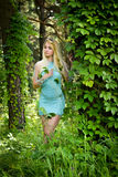 Pretty young blonde girl with closed eyes and long hair in turquoise dress standing in the green forest where trees are enlaced wi Stock Photo