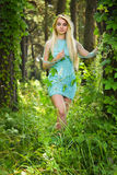 Pretty young blonde girl with closed eyes and long hair in turquoise dress standing in the green forest where trees are enlaced wi Royalty Free Stock Photo