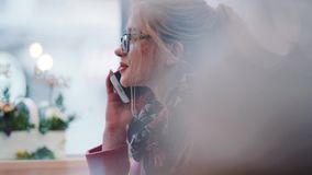 Pretty young blonde girl in a glasses sitting in the cozy café, having a phone call, smiling, nodding. Agreement. Pretty young blonde girl in a glasses sitting stock footage