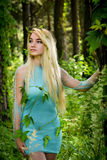 Pretty young blonde girl with long hair in turquoise dress standing in the green forest Royalty Free Stock Images