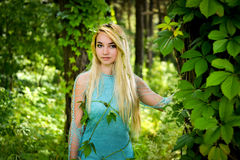 Pretty young blonde girl with long hair in turquoise dress standing in the green forest Royalty Free Stock Photos