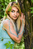 Pretty young blonde girl with long hair in turquoise dress standing in the green forest Stock Image