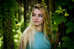 Pretty young blonde girl with long hair in turquoise dress Stock Photos