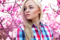Pretty young blonde girl looking away with pink flowers behind Stock Image