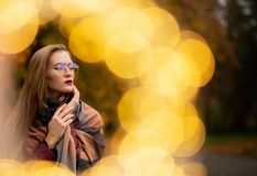 Pretty young blonde girl playing with fairy lights at the autumn royalty free stock photos