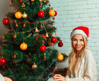 Pretty young blonde girl in santa hat near christmas tree smilin Royalty Free Stock Photos