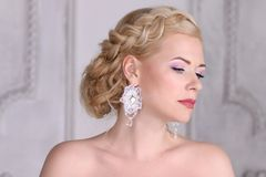 Pretty young blonde with hairdo and in earrings. Poses in white studio Stock Image