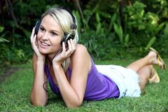 Pretty Young Blonde Lady with Earphones. Gorgeous young lady listening to music while relaxing on the green grass Royalty Free Stock Image