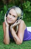 Pretty Young Blonde Lady with Earphones. Gorgeous young lady listening to music while relaxing on the green grass Stock Images