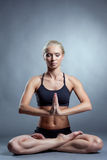 Pretty young blonde meditating in lotus position Stock Photo