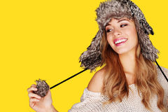 Pretty Young Blonde Playing With Pompom. Carefree pretty young blonde woman playing with the pompom on her winter hat Stock Image