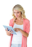 Pretty young blonde using her tablet pc Royalty Free Stock Image