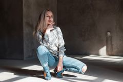 Pretty young blonde in a vintage stylish shirt in blue trendy ripped jeans in green trendy cowboy boots posing sitting. In a room with sunlight. Sexy beautiful royalty free stock image