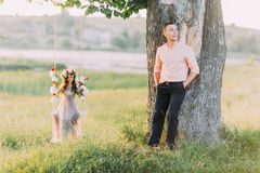 Pretty young blonde wearing lilac dress and wreath sitting in swing while her handsome boyfriend standing near tree Royalty Free Stock Photography