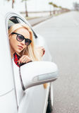 Pretty young blonde woman looks out from car window stock images